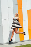 Portrait of trendy fashion girl in sunglasses. On the background color of orange wall Stock Photos