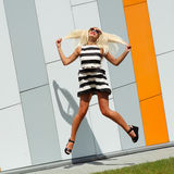 Portrait of trendy fashion girl in sunglasses. On the background color of orange wall Royalty Free Stock Photography