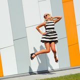 Portrait of trendy fashion girl in sunglasses. On the background color of orange wall Stock Photography