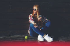 Portrait of a trendy funky women chatting on her cell telephone during recreation time in summer day Stock Photo