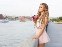 Portrait of Trendy Girl with Dreads and Vintage Camera Standing by the River. Modern Youth Lifestyle Concept. Stock Photos