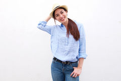 Trendy happy woman standing with hand to hat Royalty Free Stock Photo
