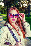 Portrait of Trendy Redhair Girl Standing in the park lane. Urban Fashion Concept  Red Lips and funny sunglasses.  Toned Royalty Free Stock Photography