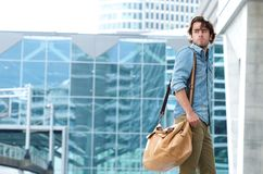 Portrait of a trendy young man walking. In urban area with bag Royalty Free Stock Image