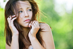 Portrait of troubled brunette girl. Portrait of troubled beautiful brunette girl looking somewhere at summer green park Royalty Free Stock Images