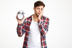 Portrait of a troubled man holding alarm clock stock photos