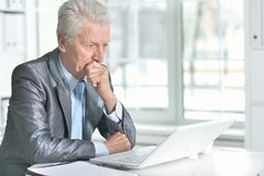 Portrait of troubled senior man using laptop. Troubled senior man in formal wear using laptop in office stock photography