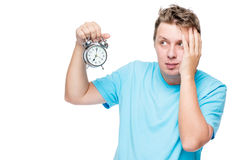 Portrait of a troubled sleepy man with an alarm clock. On white background Stock Images