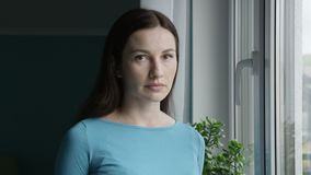 Portrait of Troubled Woman with Sad Neutral Face Expression Standing at the Window Looking at Camera Shot on Red
