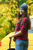 Portrait of turning around guitar player girl wearing slouchy beanie hat at yellow van background Royalty Free Stock Image