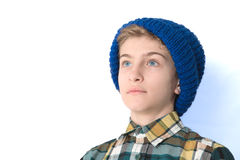 Portrait of a Tween Boy in a hat. Portrait of a Tween Boy with a blue hat.  Isolated studio shot of a young pre-adolescent boy.  He gazes in contemplation Stock Photo