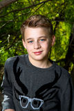 Portrait of a Tween Boy. Leaning on a tree with a cocky expression. He has big, blue eyes, blond hair, and is wearing a sweather Royalty Free Stock Photo