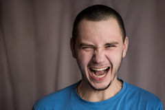 Portrait of a twenty-year-old man in a blue shirt and plaid shirt with natural light with flash on a white background, screaming m Stock Photography