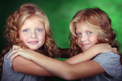Portrait of twin girls holding each other. Little twin sisters holding each other Royalty Free Stock Image