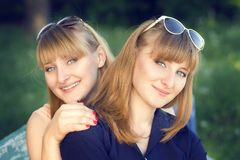 Portrait of twins sisters at the park Royalty Free Stock Photography