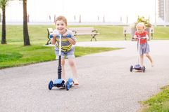 Two active little children friends girl and boy riding scooters on road in park outdoors. Portrait of two active little children friends girl and boy riding royalty free stock image