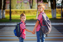 Portrait two adorable boys with backpack near pedestrian crossin royalty free stock images