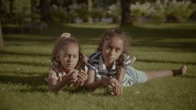 Portrait of adorable sisters lying on green grass. Portrait of two adorable elementary age african american sisters lying on green grass and smiling while stock footage