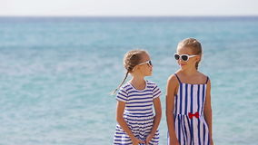 Portrait of two adorable little girls together during beach vacation. Adorable little sisters at beach during summer vacation stock footage