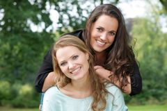 Portrait of two adult sister smiling together outdoors Royalty Free Stock Photography