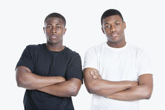 Portrait of two African American male friends with arms crossed over gray background Royalty Free Stock Photo