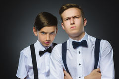 Portrait of two angry boys isolated on gray background. Negative human emotion, facial expression. Closeup Stock Photos
