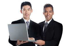Portrait of two Asian professionals presenting. Two Asian businessmen, Chinese and Malay, holding a laptop together signifying racial harmony and international Royalty Free Stock Photos