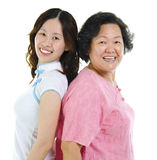 Portrait of two Asian women. Back to back, over white background Royalty Free Stock Photos