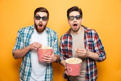 Portrait of a two astonished young men in 3d glasses. Eating popcorn while standing isolated over yellow background stock images