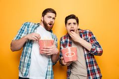 Portrait of a two astonished young men eating popcorn. While standing isolated over yellow background royalty free stock image