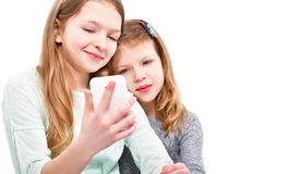 Portrait of two attractive girls, taking selfie on mobile phone royalty free stock images