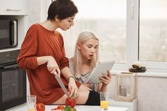 Portrait of two attractive women sitting in kitchen and reading something in tablet, expressing curiosity and interest. While preparing salad. Girls passing royalty free stock photography