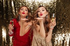 Portrait of two attractive young girls in shiny dresses. Holding glasses with champagne while sending air kiss and celebrating isolated over golden shiny Royalty Free Stock Image