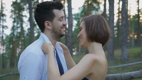 Portrait of two attractive young people, guys and girls in the pine forest. The beautiful husband and wife walking in the park on a warm summer evening stock footage