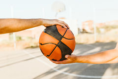 Portrait of two basketball players holding a basket ball on cour Stock Photography