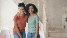Portrait of two beautiful african american girls laughing and looking into camera. Women show emotions from serios face stock video