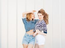 Portrait of two beautiful fashionable girlfriends in denim shorts and striped t-shirt posing nex to the glass wall. Girl showing t Royalty Free Stock Photo