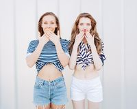 Portrait of two beautiful fashionable girlfriends in denim shorts and striped t-shirt posing nex to the glass wall. Have positive Royalty Free Stock Photos