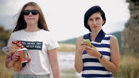 Portrait of two beautiful female friends with coffee and smartphone in the old town stock video footage