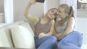 Portrait of two beautiful girls making selfies at home stock footage