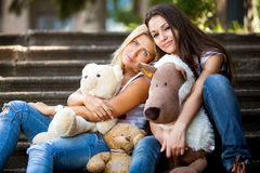 Portrait of two beautiful girls sitting on stairs with teddy bears Stock Image