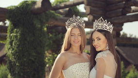 Portrait of two beautiful girls in wedding dresses. And tiaras outdoors in the park stock footage