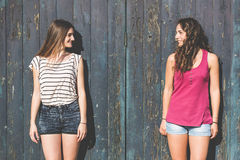 Portrait of two beautiful girls with wooden background Stock Photo
