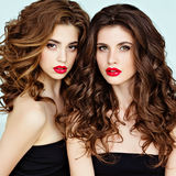 Portrait of two beautiful, glamorous, sensual brunette with gorg. Eous curly hair and bright makeup with red lipstick, close-up, beauty Stock Image
