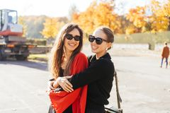 Portrait two beautiful happy girlfriends in the park. Portrait two beautiful happy girlfriends on a sunny autumn day have fun royalty free stock photo