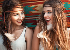 Portrait of two beautiful hippie girls having fun and laughing,. Looking each other Stock Photo