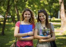 Portrait of two beautiful students in the park.  Royalty Free Stock Photo