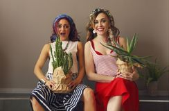 Portrait of two beautiful women in bright clothing and bow in head with bright lips holding cactuses royalty free stock photos