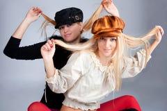 Portrait of two beautiful women wearing caps stock image
