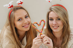 Portrait of two beautiful young girls doing sweet heart with Chr Stock Photos
